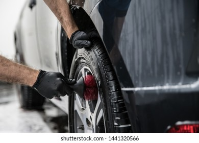 Man cleaning car wheel with brush. Car wash
