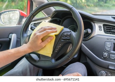 Man is cleaning car wheel and dashboard with microfiber cloth.