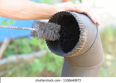 Man cleaning chimney pipe outside. Cleaning a wood burning stove. Chimney sweep cleaning