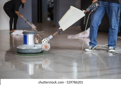 The man cleaning floor with machine.