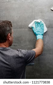 Man cleaning a gray tile bathroom shower wall with a wet cloth while wearing a protective glove. Gray tile bathroom shower wall being cleaned with a cloth rag by a man wearing a cleaning glove.