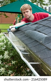 A Man Cleaning Gutters With A Water Hose