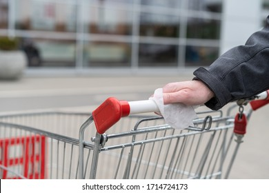 Man cleaning handle of shopping cart, trolley using antivirus antibacterial wet wipe (napkin) for protect himself from bacteria and virus. grocery store, supermarket