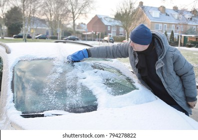 A man is cleaning his car with an ice scraper