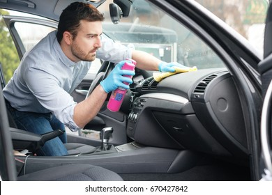Man cleaning his car interiors and dashboard