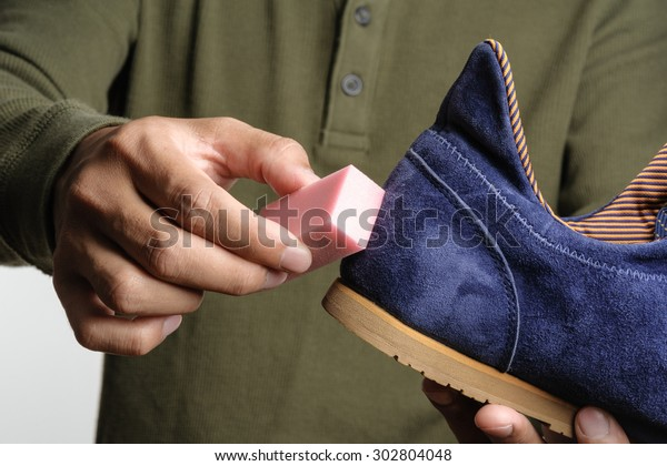The man cleaning his suede shoe