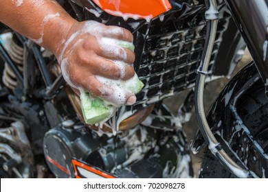 A man cleaning a motorcycle with a green sponge using foam.