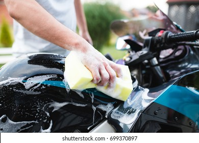 A man cleaning motorcycle with sponge, motorcycle detailing (or valeting) concept. Selective focus.