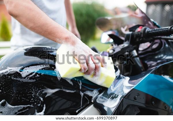 スポンジとオートバイ、詳細な(またはバレッティング)コンセプトを持つ男性用バイクを清掃する男性。限定フォーカス。