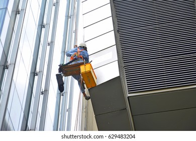 A man cleaning on a high  building