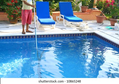 man cleaning pool with large pole and lots of flowers