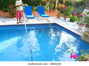man cleaning pool with lots of flowers