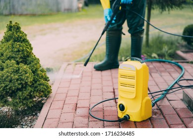 Man cleaning red, conrete pavement block using high pressure water deck. Paving cleaning concept. Man wearing waders, protective, waterproof trousers and gloves doing spring jobs in the garden.