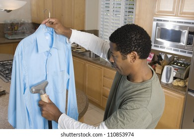 Man Cleaning Shirt With Vacuum Cleaner