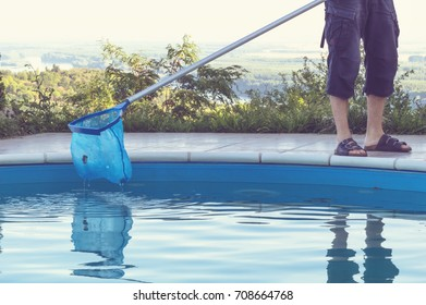 Man cleaning swimming pool of fall leaves with cleaning net in the morning.