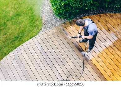 man cleaning terrace with a power washer - high water pressure cleaner on wooden terrace surface