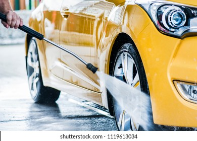 Man cleaning vehicle with high pressure water spray or jet. Car wash details.