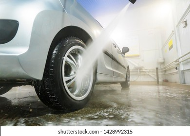 Man cleaning vehicle with high pressure water spray or jet. Car wash details. wash the wheels with water. washing the rear wheel of a car