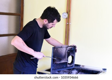 Man cleaning wood burning stove. Cleaning a stove for central heating