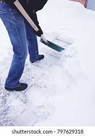 The man cleans the snow with a shovel.