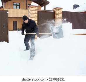 Man cleans snow shoveling around the house.