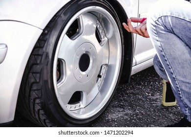 A man cleans the wheels of his car. Dropped silver car on air suspension.