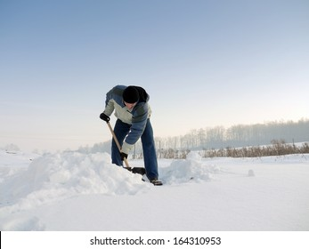 Man clearing his backyard with shovel after heavy snowfall