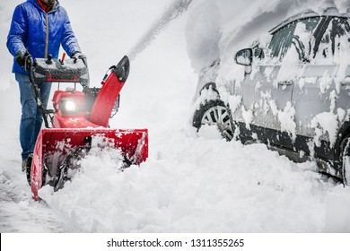 Man clearing or removing snow with a snowblower on snowy road detail.