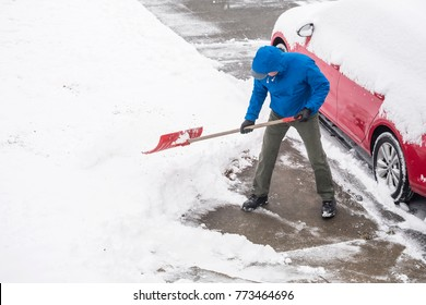 Man Clearing Snow in His Driveway with a Shovel