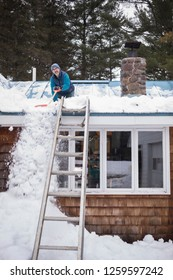 Man clearing snow off a blue metal roof in Maine.