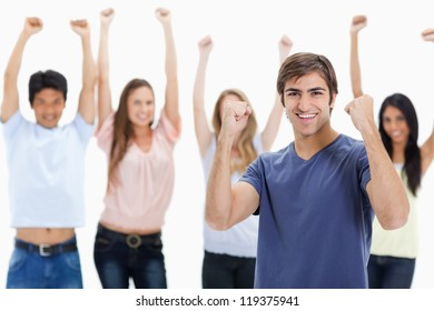 Man clenching his fists with people behind him raising their arms against white background