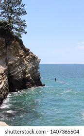 man cliff jumping into ocean