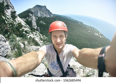 man climber makes selfie photography with mountains and sea background