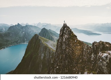Man climber standing on cliff mountain edge above fjord in Norway travel adventure extreme lifestyle journey vacations solitude emotions mountains landscape