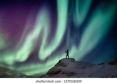 Man climber standing on snowy peak with aurora borealis and starry in the night sky