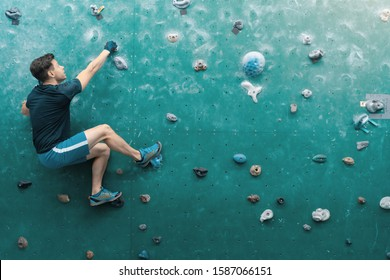A man climbing in boulder gym in the wall.