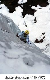Man climbing a frozen waterfall