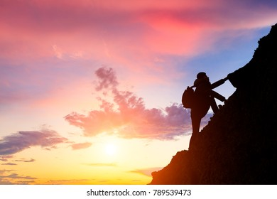 man climbing mountain at sunrise,conceptual scene