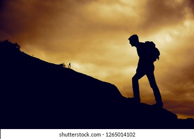 Man climbing up a mountain in sunset
