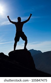 Man climbing in mountains, arms outstretched, success concept. Silhouette of climber and blue summer sky, extreme sport and exercising outdoors.