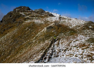 Man climbing a Munro mountain in the Scottish hihglands on a winters day