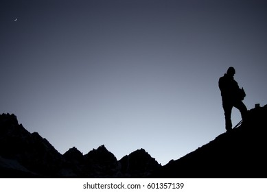 Man climbing on the mountains at night.