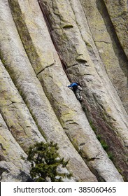 Man climbing on the wall of famous mountain Devils Tower in the Black Hills (Wyoming).