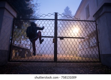 Man climbing over a fence in the night fog.