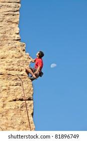 Man climbing a rock face next to the moon