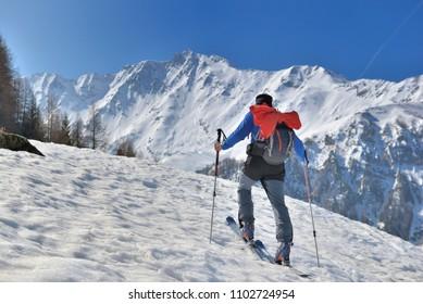 man climbing snowy mountain in touring ski under blue sky
