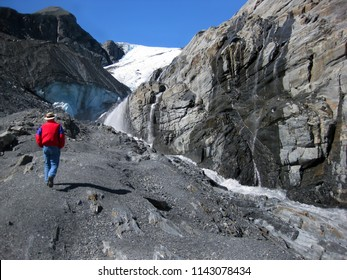 Man climbs to get a better view of Worthington Glacier in the Thompson Pass outside of Valdez.  Small waterfalls trickle down cliff walls into a glacier stream.