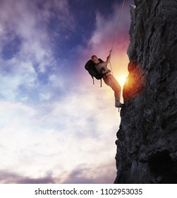 Man climbs a high danger mountain with a rope during sunset