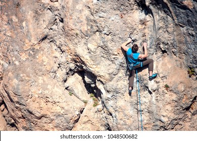 A man climbs the rock. Climbing in nature. Fitness outdoors. Active lifestyle. Extreme sports. The athlete trains on a natural relief.