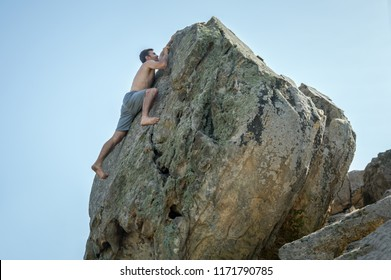 A man climbs up the rock mountain, climbing upwards